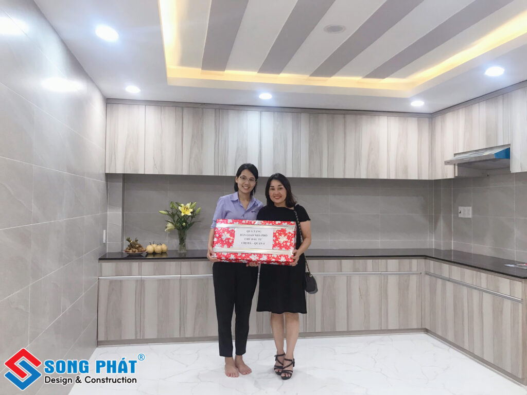 Chị Trần Thị Lý – PGĐ tặng quà bàn giao chụp hình cùng chị Hà chủ Nhà.